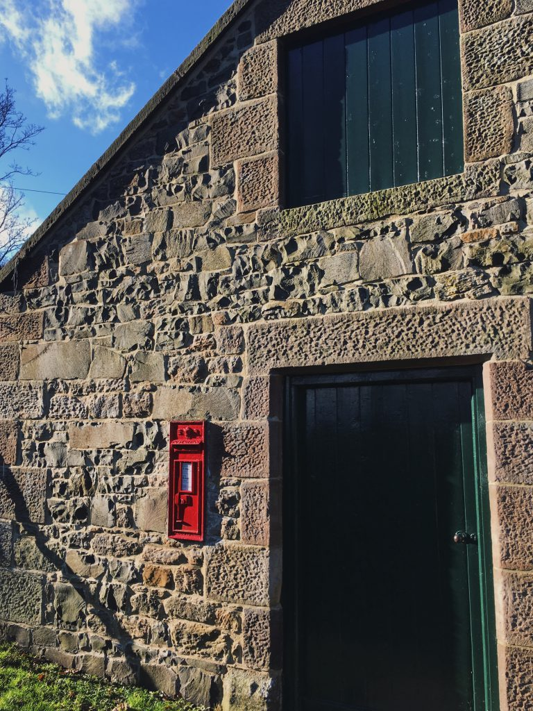 A small post box on a stone building in the Scottish Borders